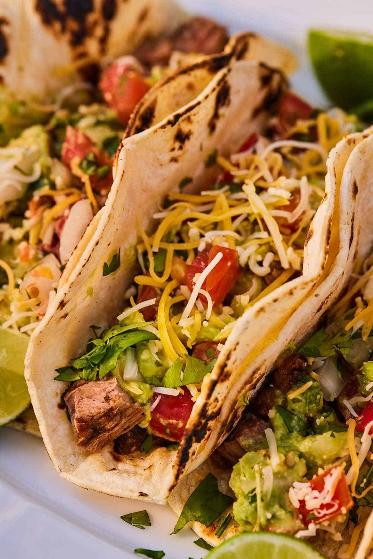 Close up a carne asada taco with shredded cheese, pico de gallo, and guacamole.