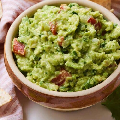 A bowl of guacamole with a linen napkin, tortilla chips, and a lime wedge surrounding it.