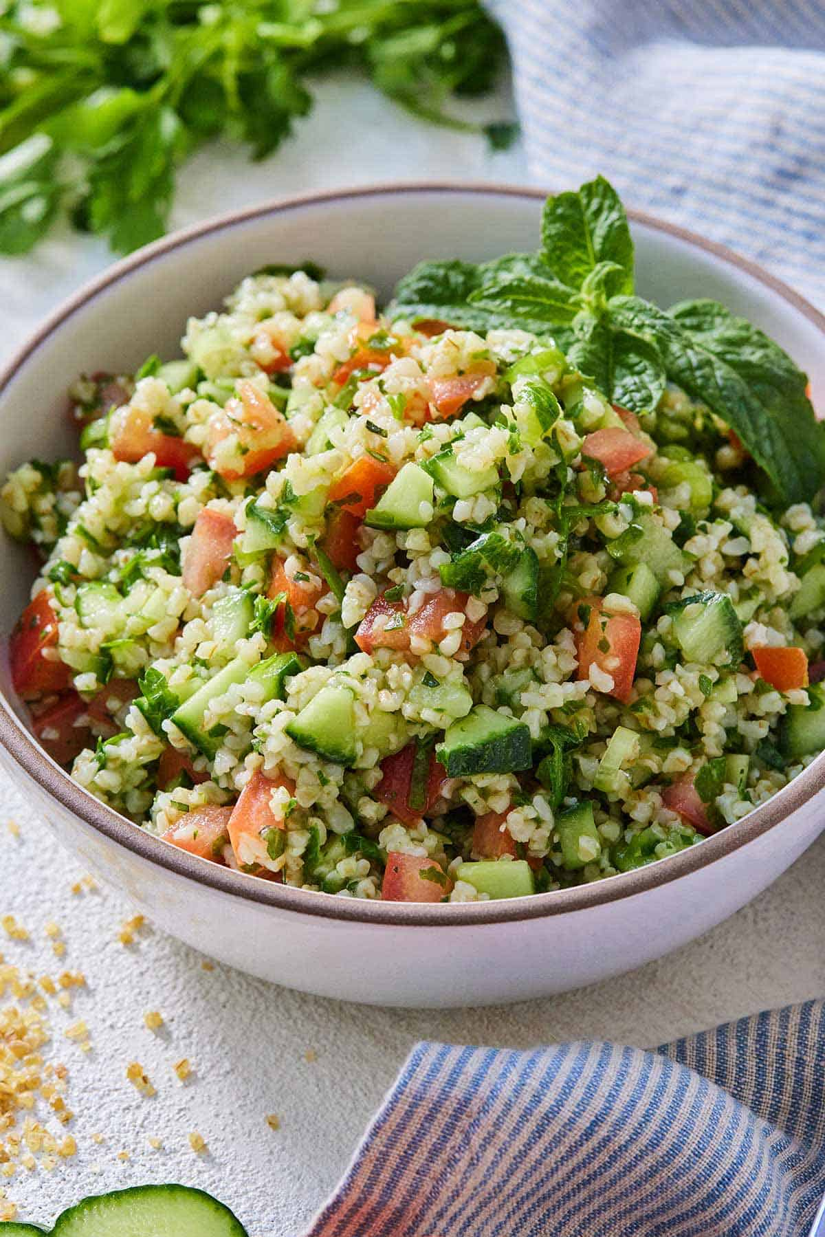 A bowl of tabbouleh topped with fresh mint as a garnish and beside a blue and white striped linen.