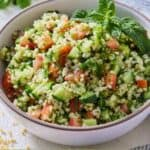 Pinterest graphics of a bowl of tabbouleh with fresh herbs on top by a striped linen.