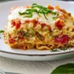 Pinterest graphic of a plate of vegetarian lasagna with basil on top.