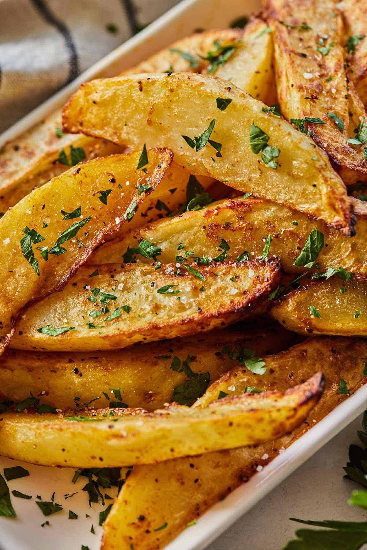 Close up image of crispy potato wedges with freshly chopped parsley as garnish.