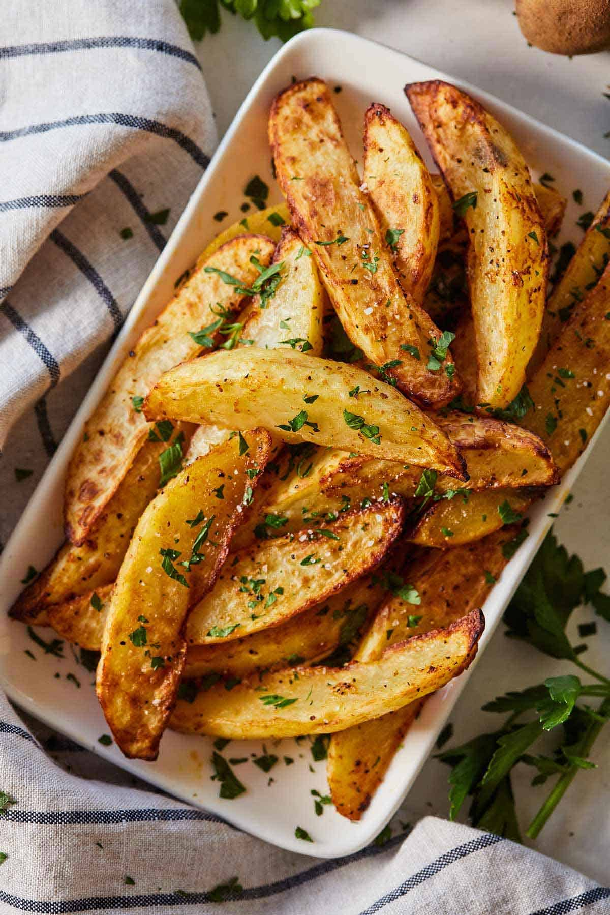 Overhead view of a bowl of air fryer potato wedges with chopped parsley on top as garnish.