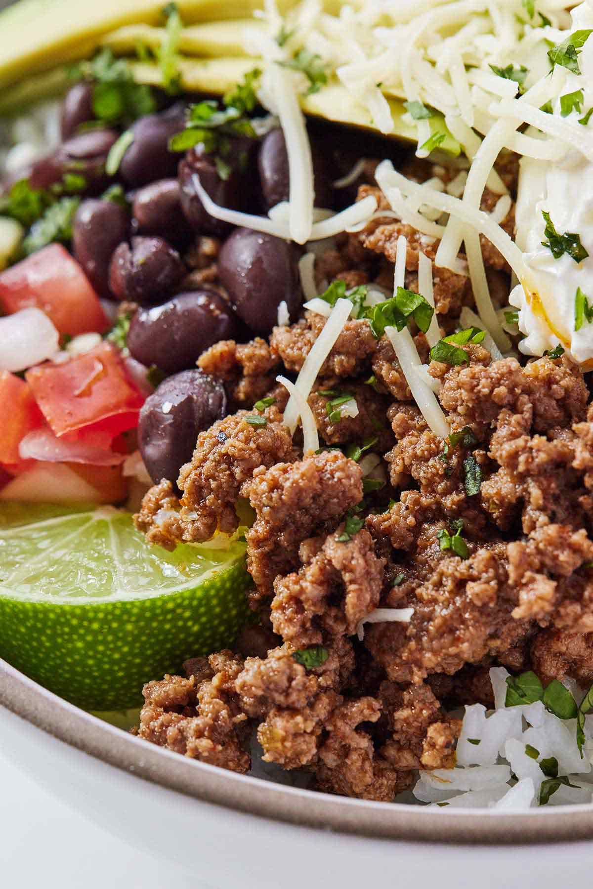 Close up of a taco bowl, with the ground beef in the foreground overtop of a bed of cilantro lime rice and some black beans, pico de gallo, a lime wedge, and cheese.