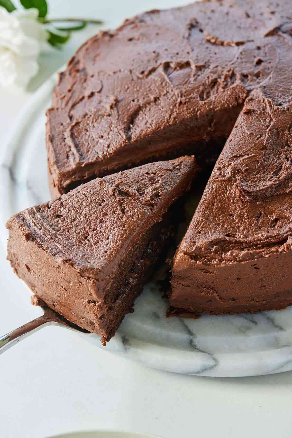 A vegan chocolate cake with chocolate frosting with a slice of the cake being removed with a cake server.