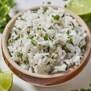 Close up of a bowl of cilantro lime rice with some wedges of lime out of focus behind it.