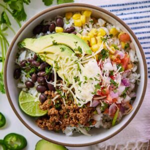 Overhead view of a taco bowl with an assortment of toppings and herb garnish.