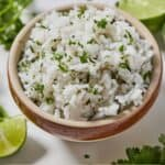 Pinterest graphic of a bowl of cilantro lime rice with cut limes and chopped cilantro surrounding it on the table.