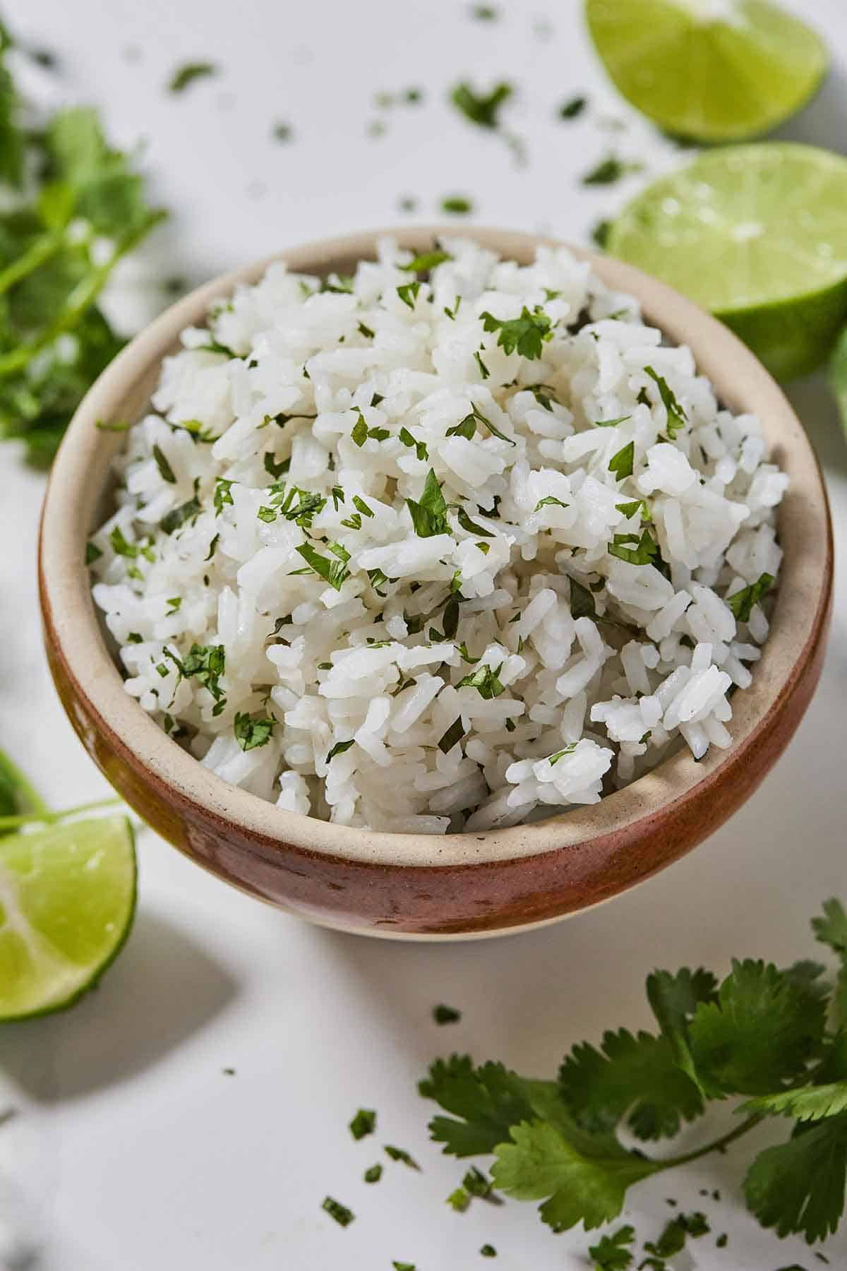 Overhead view of a bowl of cilantro lime rice with a couple of cut limes and fresh cilantros on the table.