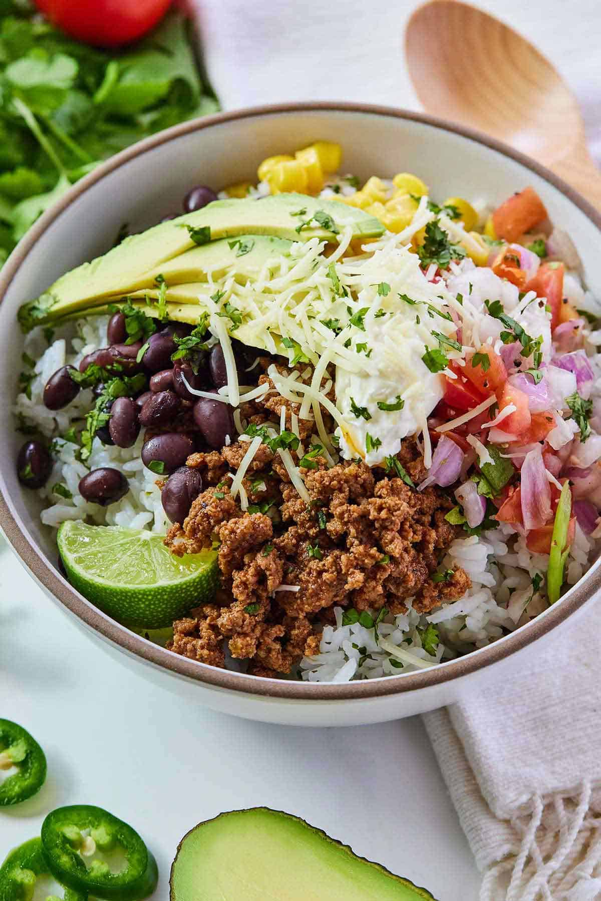 Overhead view of a ground beef taco bowl topped with pico de gallo, corn, black beans, avocado, cheese, and sour cream. Some jalapenos, cut avocado, herbs, and a wooden spoon around it.