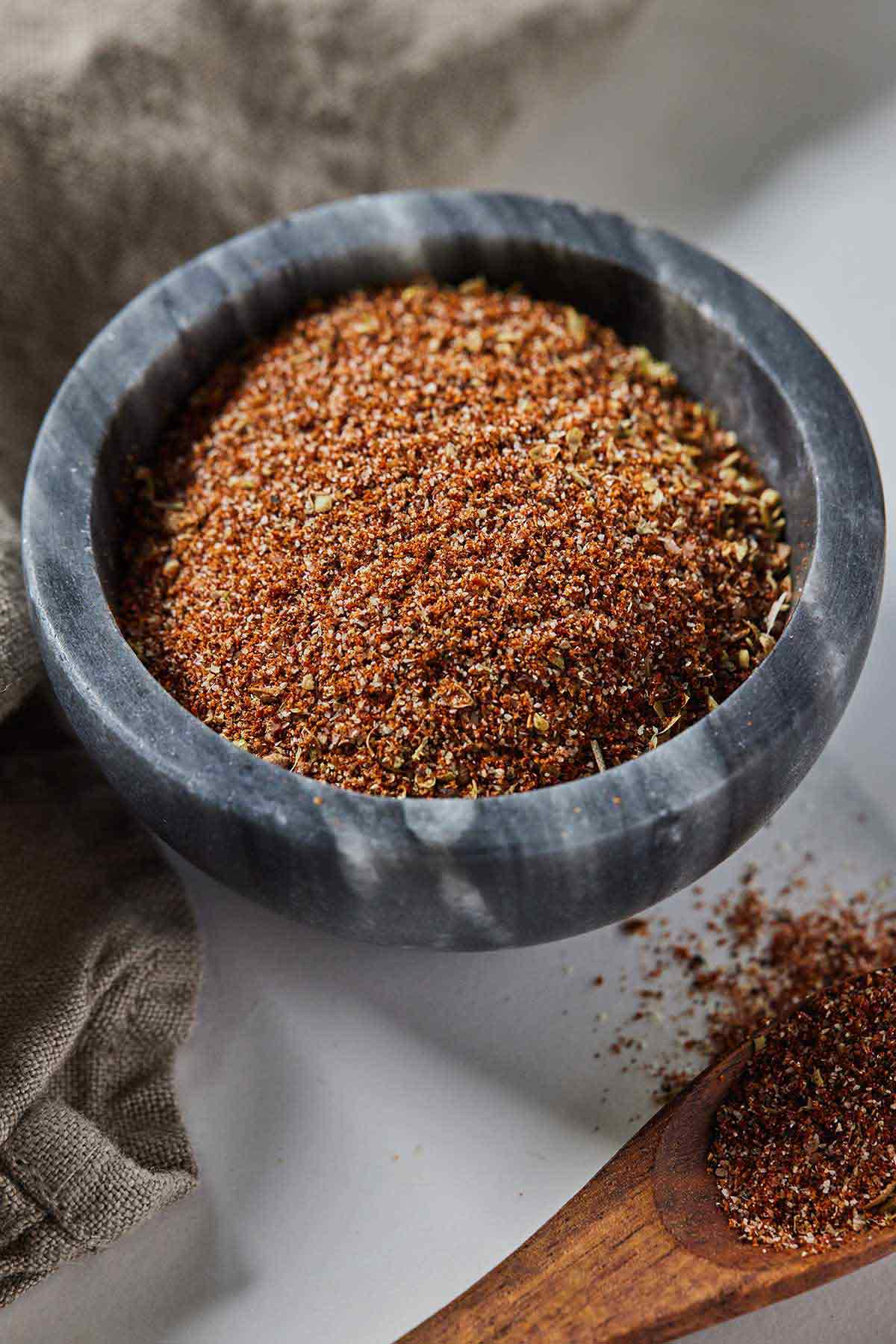 A grey pinch bowl of taco seasoning with a wooden spoon containing some beside it.