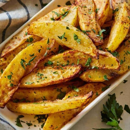 Overhead view of a serving bowl of air fryer potato wedges beside a striped linen napkin and some parsley on the table.