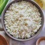 Pinterest graphic of an overhead view of cauliflower rice in a bowl with some green onions, cauliflower florets, and a lemon wedge beside the bowl.