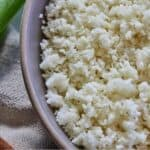 Pinterest graphic of a close up view of a bowl of cauliflower rice.