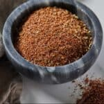 Pinterest graphic of a grey pinch bowl of taco seasoning with some on the counter beside it.