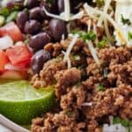 Pinterest graphic focusing on the ground beef in a taco bowl with assorted toppings.