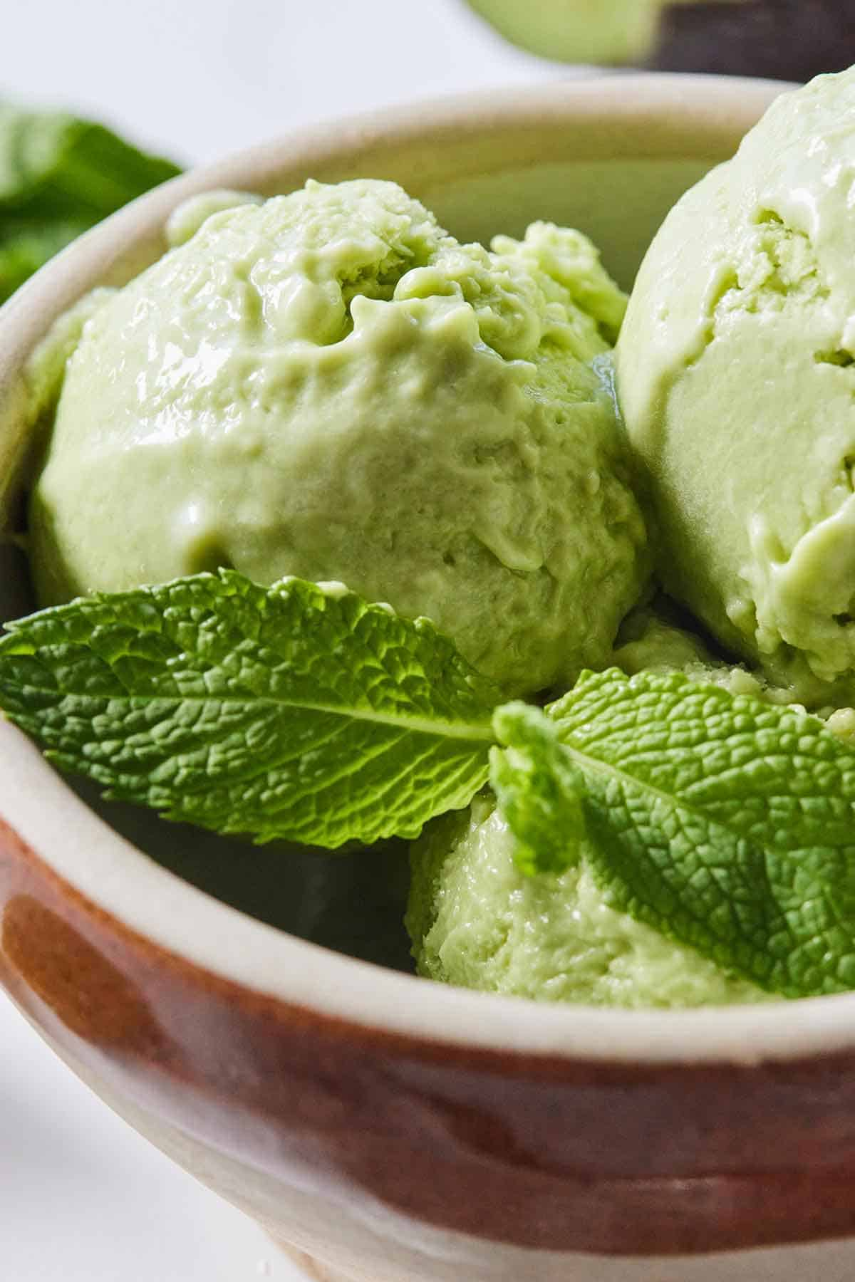 Close up of three scoops of avocado ice cream in a bowl with fresh mint on top.