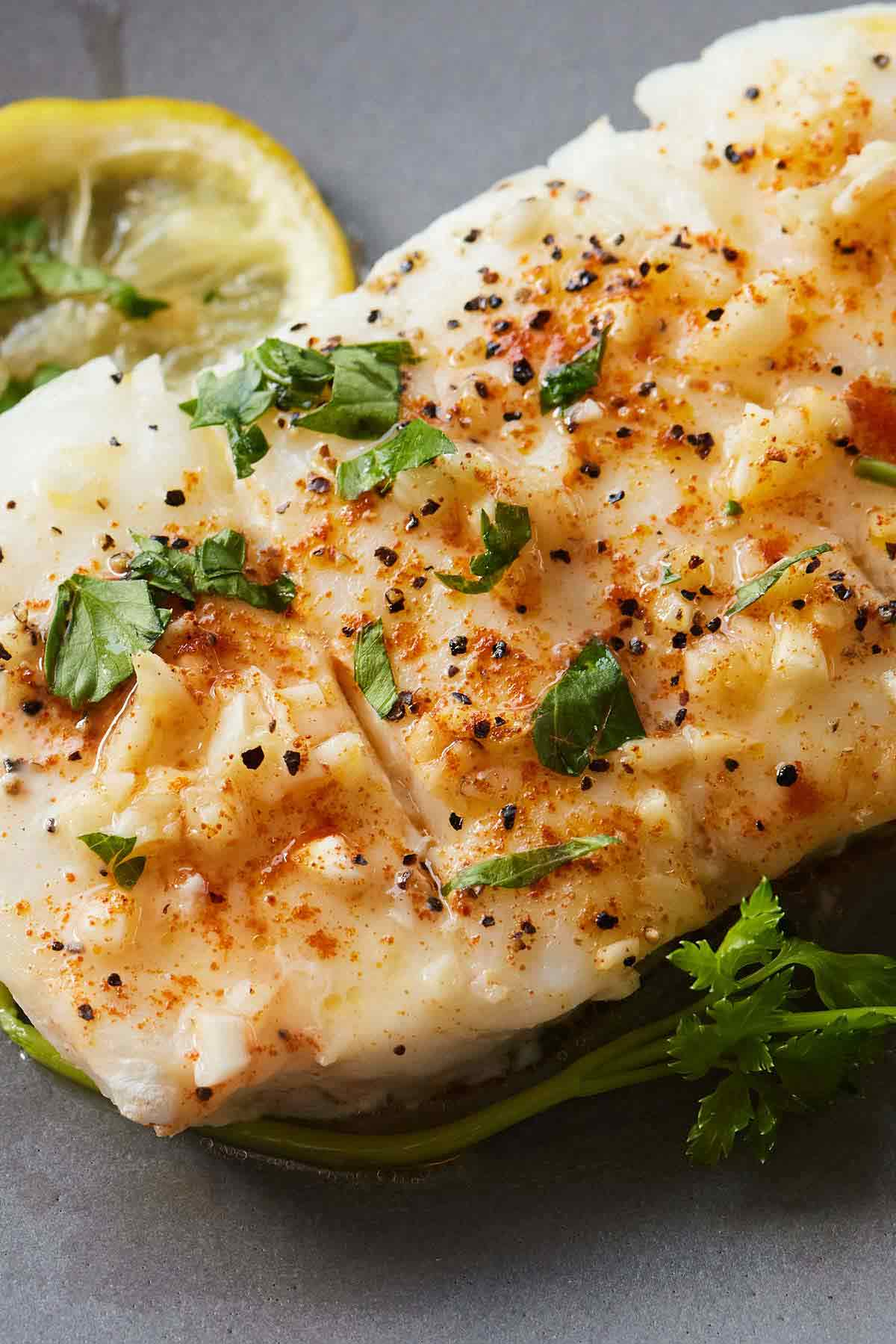 Close up of a piece of baked cod with fresh herbs and a slice of lemon.