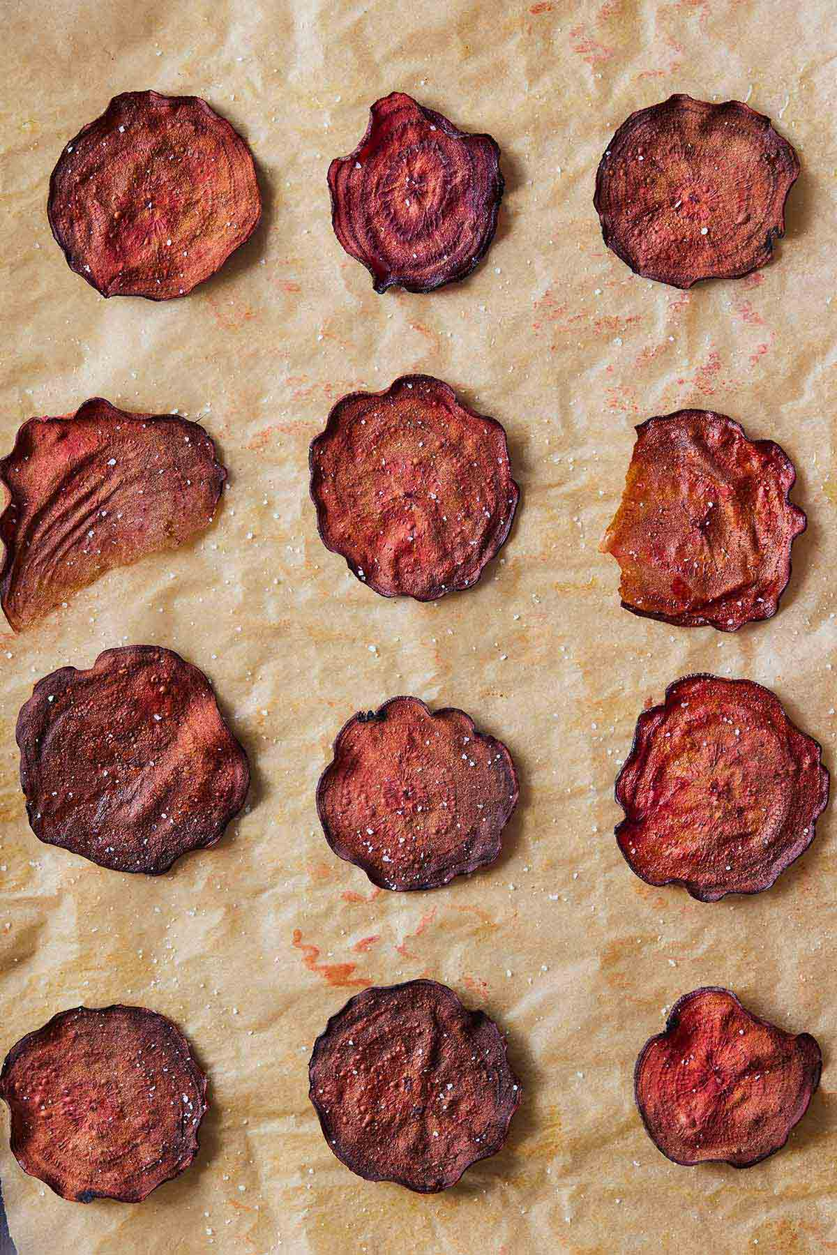 Overhead view of a parchment paper with 12 beet chips placed on top.