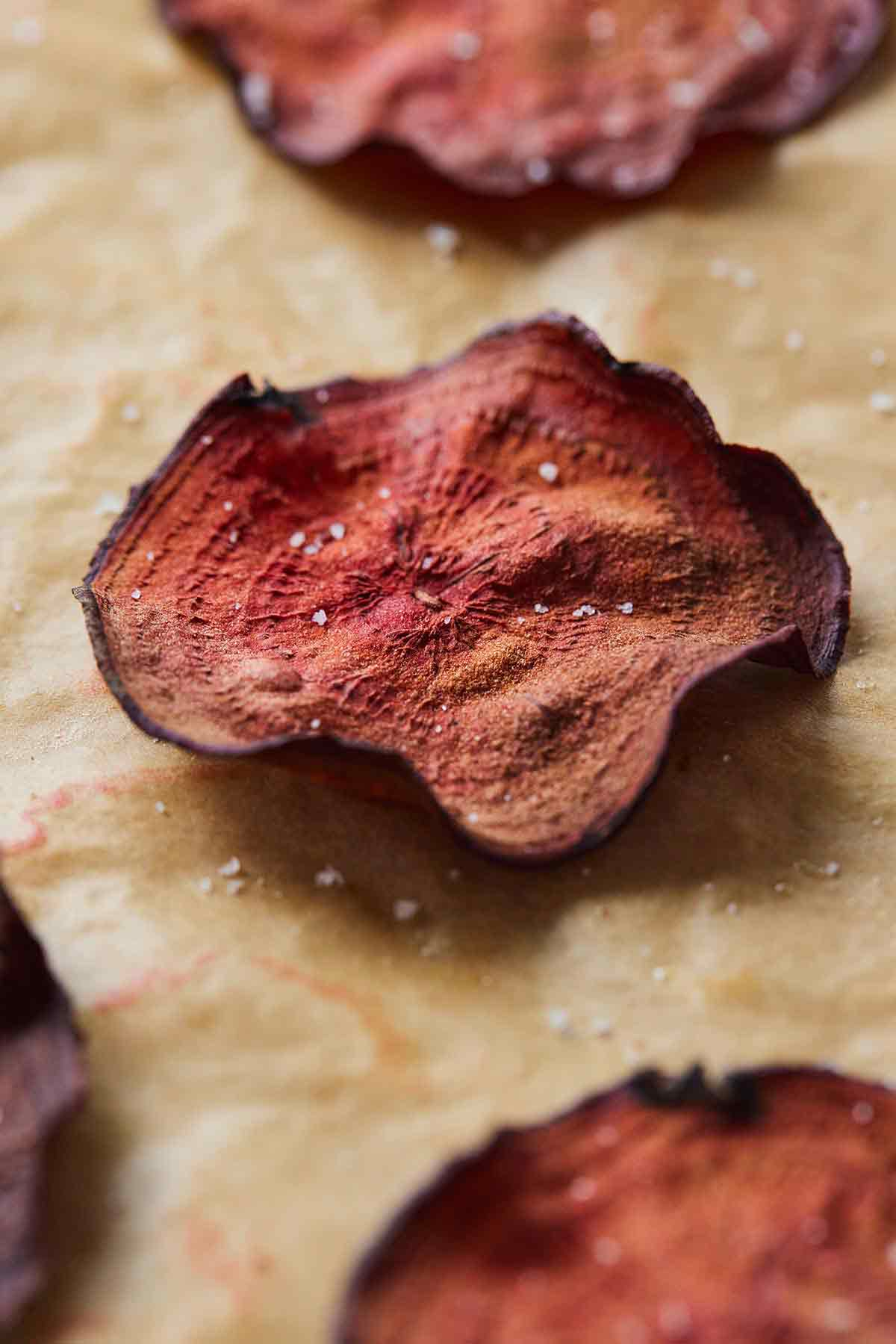 Close up of a single beet in focus with sea salt sprinkles on top.