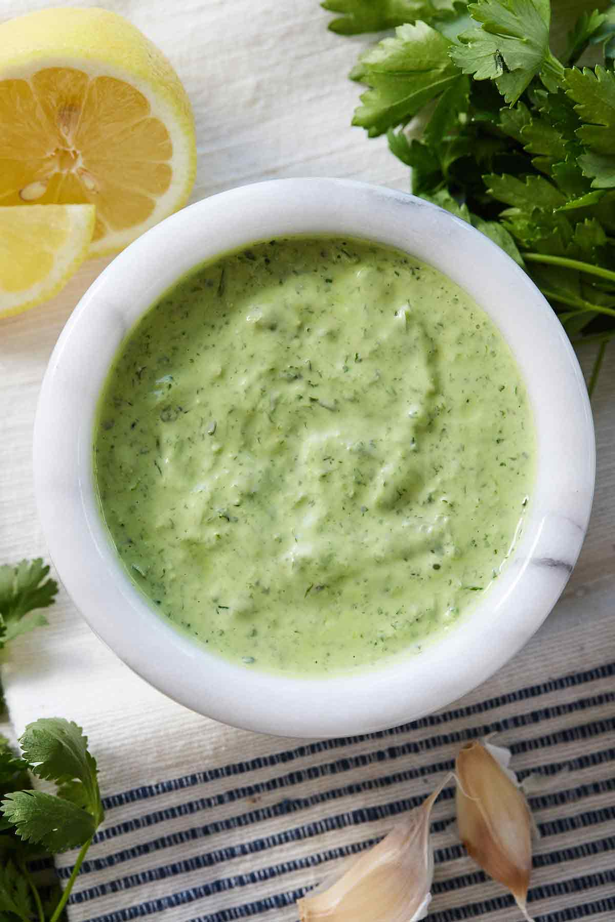 Overhead view of a bowl of green goddess dressing with fresh herbs, garlic cloves, and sliced lemon around it.
