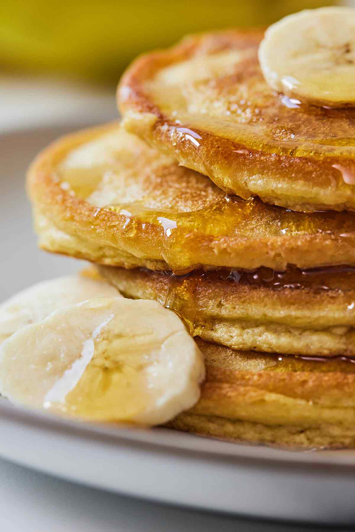 Close up of a stack of four pancakes with syrup dripping down and slices of bananas around.