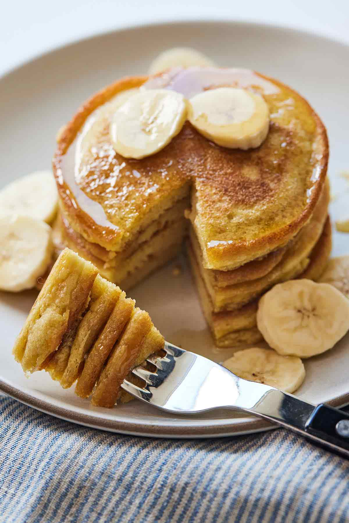Stack of paleo pancakes with pancakes on top with a wedge cut out, stuck on the fork.