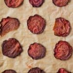 Pinterest graphic of an overhead view of beet chips on a parchment paper.