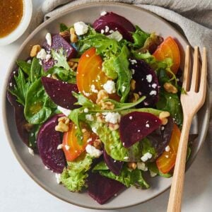 Close up of a plate of beet salad with greens and cheese with a wooden fork.