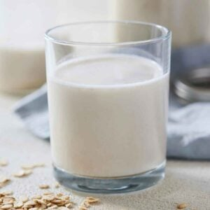 A glass of oat milk with scattered oatmeal in front and a blue linen napkin in the back.