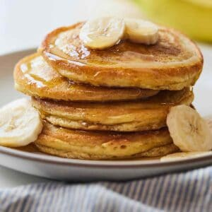 A plate of four paleo pancakes with sliced bananas.