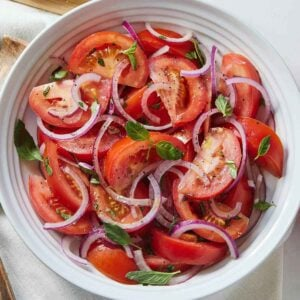 Overhead view of a bowl of of tomato salad topped with basil.