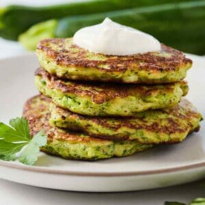 Side view of a stack of four zucchini fritters on a plate with parsley as garnish.