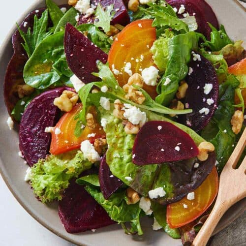 Overhead view of a plate of beet salad with a fork in the plate.