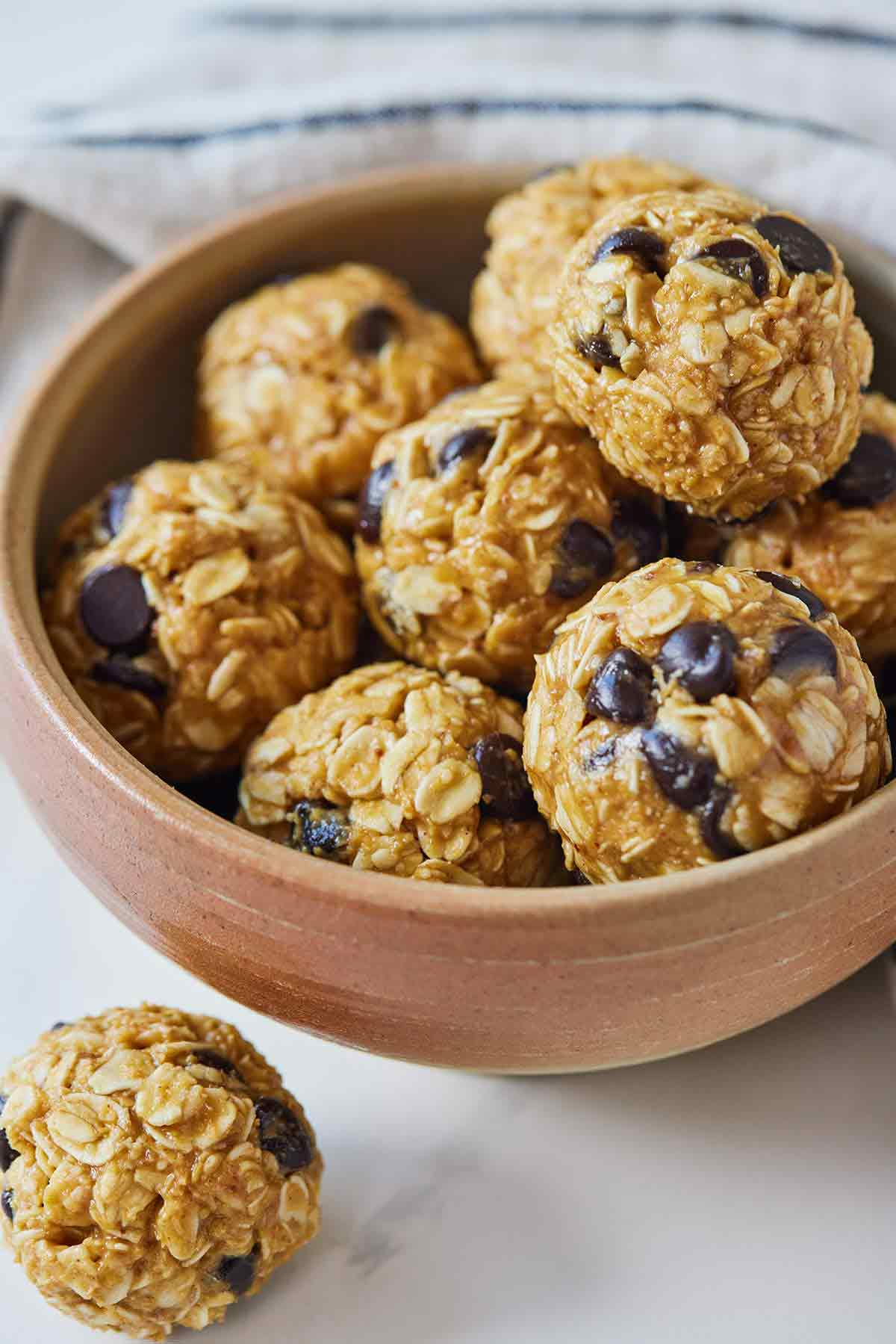 A bowl of multiple energy balls with a single one out on the counter.
