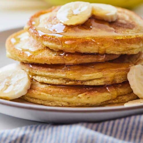 A stack of paleo pancakes with sliced bananas on top and around the pancakes with syrup dripping down.