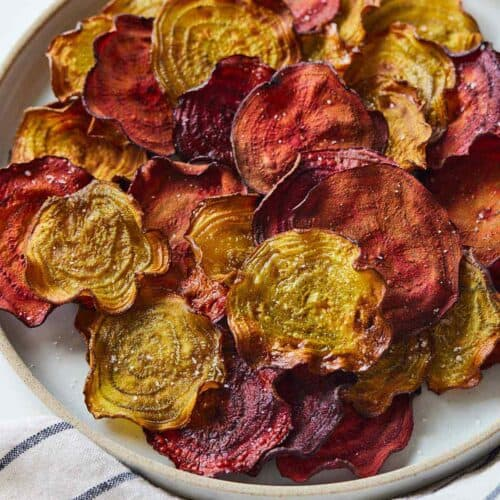 Overhead view of a plate of multi-colored beet chips.