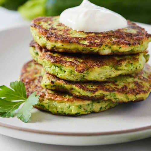 A plate of zucchini fritters with sour cream on top and some zucchinis in the background, out of focus.