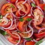 Pinterest graphic of a bowl of tomato salad with fresh basil on top.