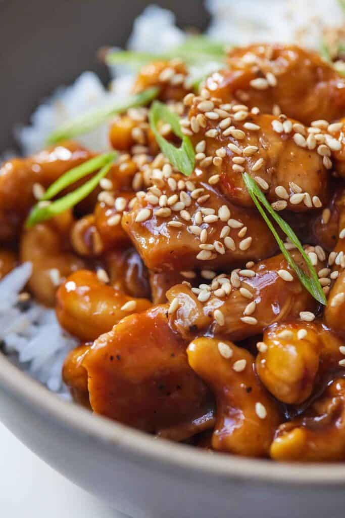 Close up of cashew chicken with green onion and sesame seeds as garnish.