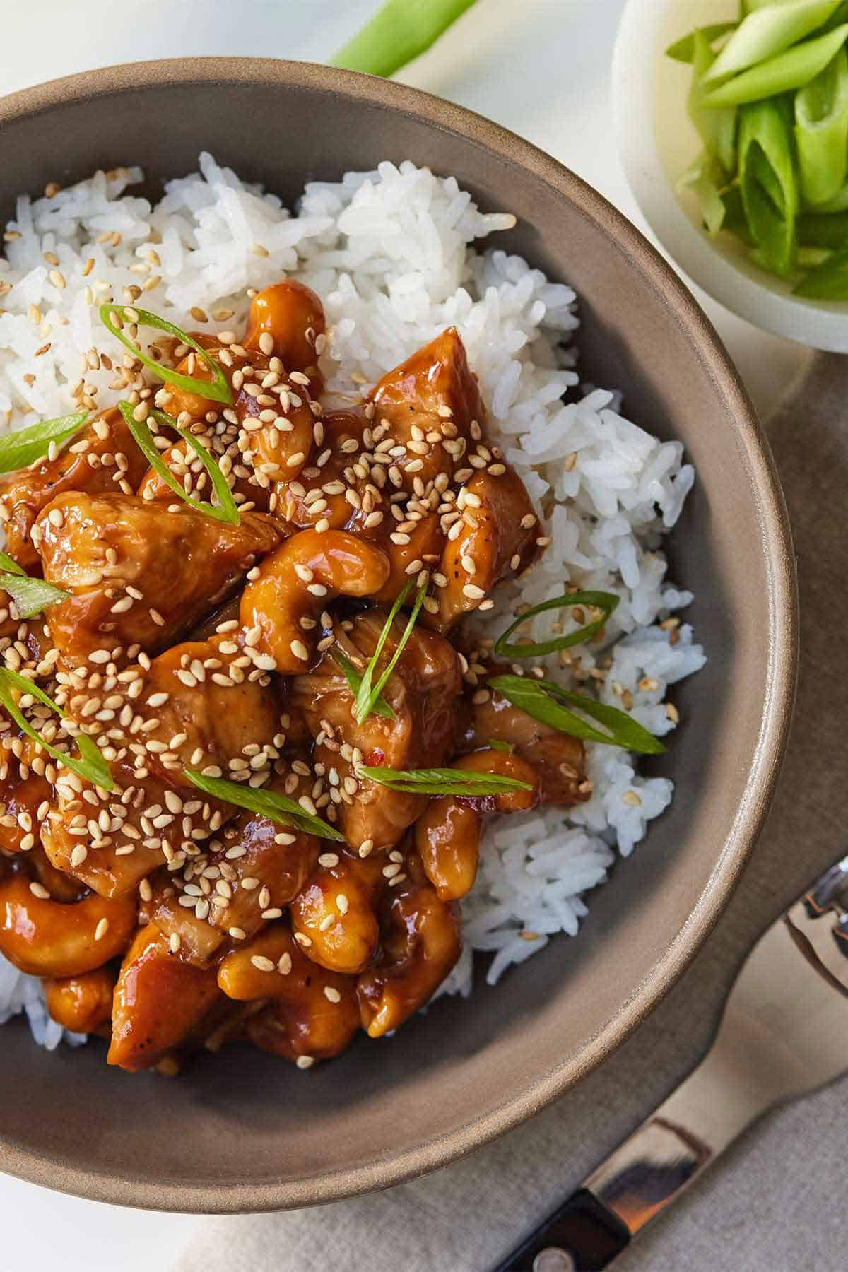 Overhead view of a bowl of cashew chicken over top a bed of rice.