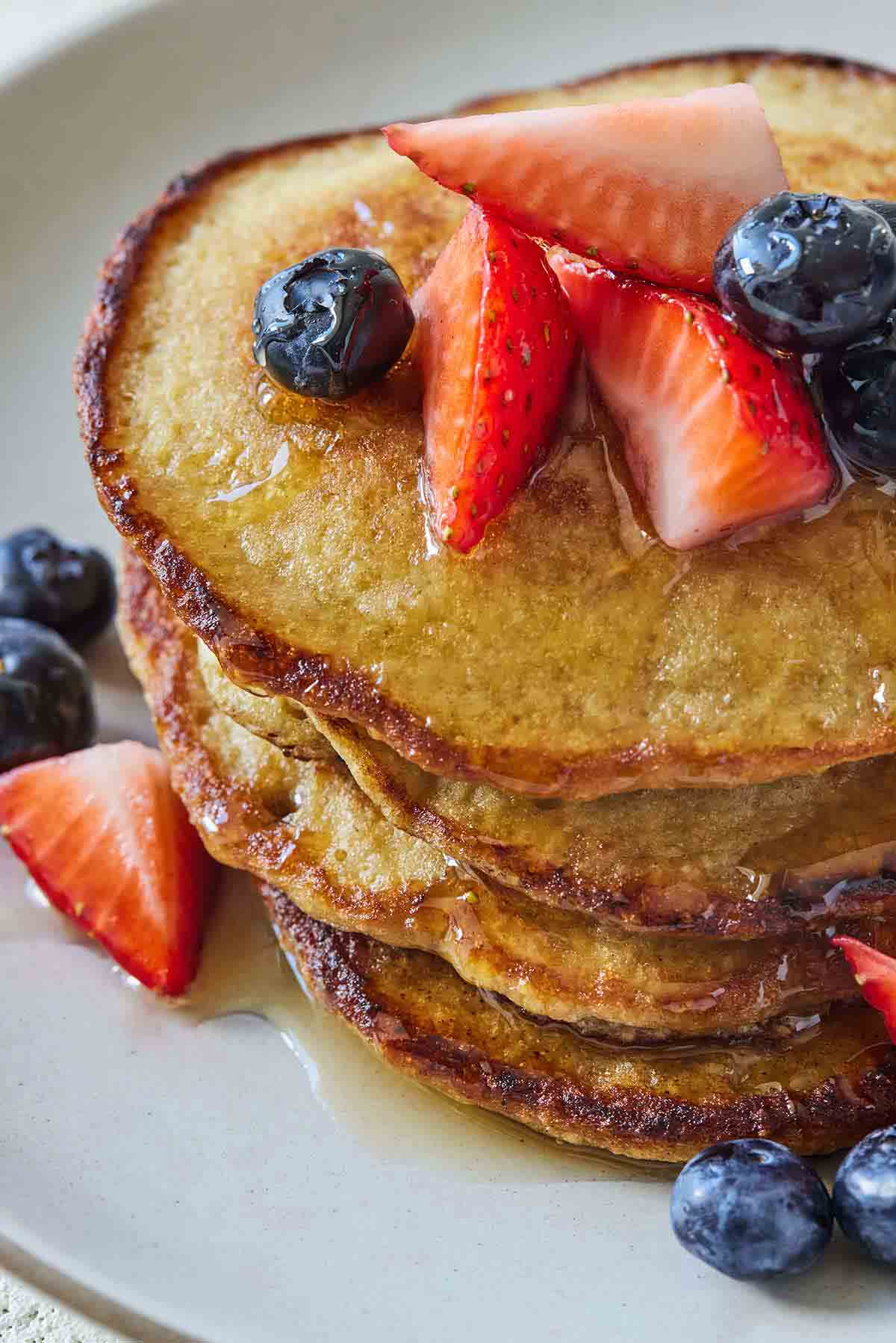 A stack of oatmeal banana pancakes with syrup, strawberries, and blueberries on top.