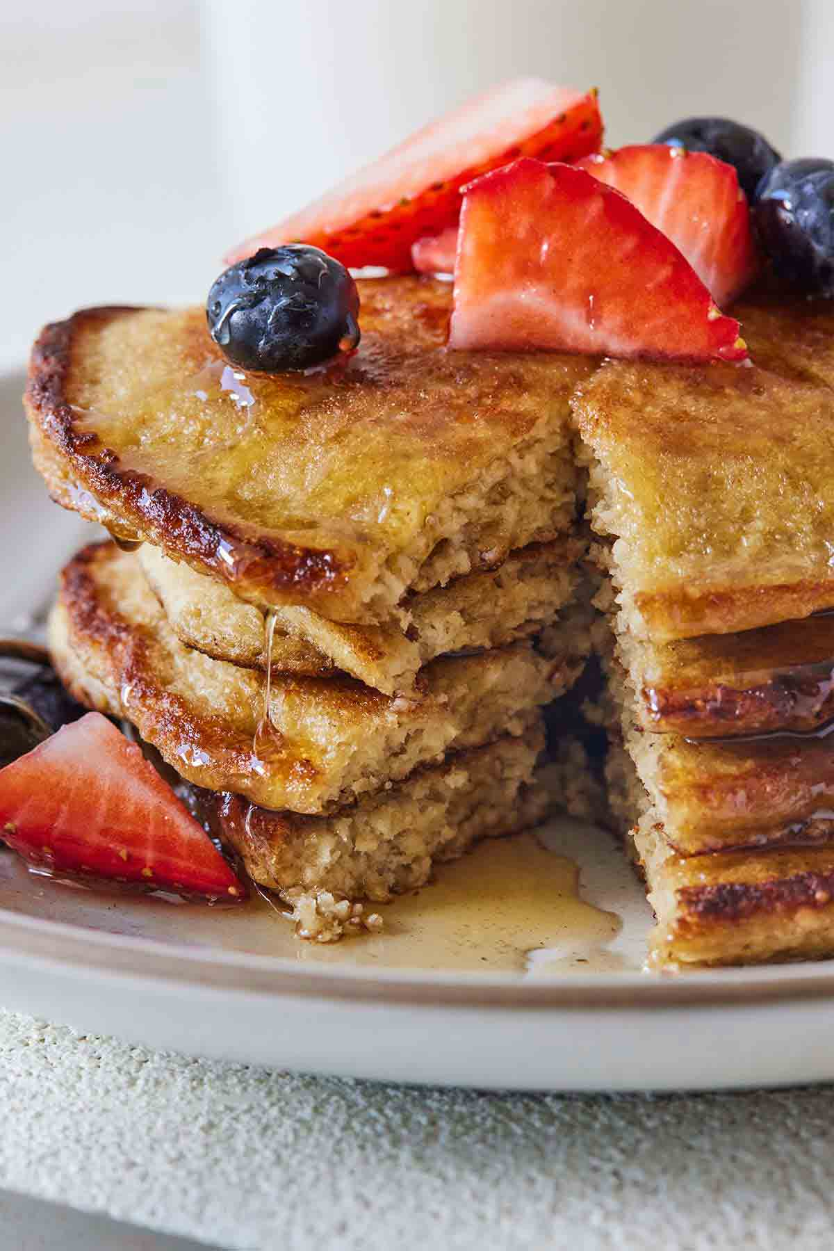 A stack of cut oatmeal banana pancakes with fruit on top.