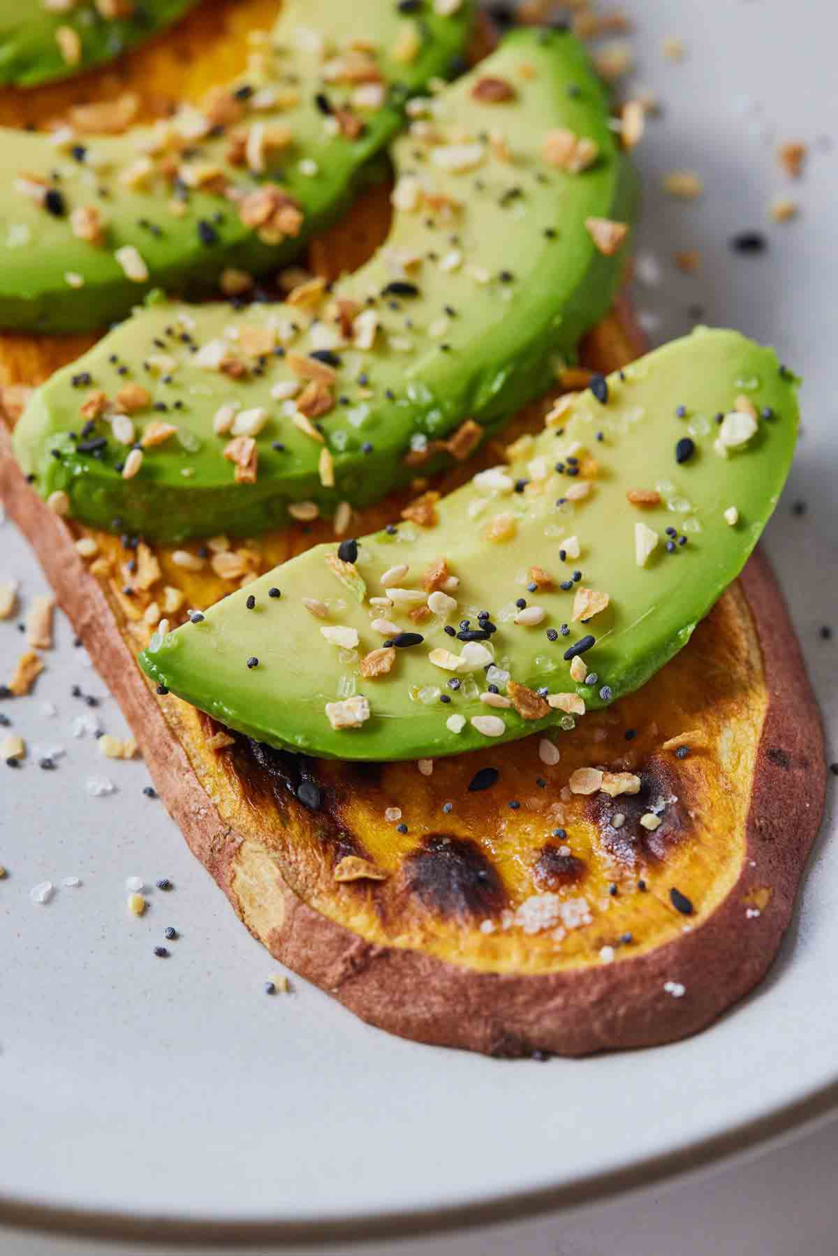 Close up of a slice of sweet potato toast with sliced avocado and everything bagel seasoning sprinkled on top.