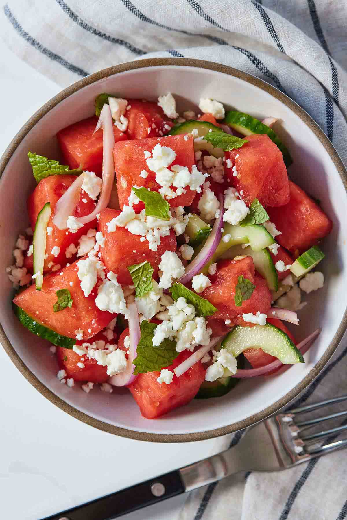 Overhead view of a bowl of watermelon salad with torn mint leaves and feta on top with a fork on the side.