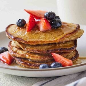 Close up of a stack of oatmeal banana pancakes with fruits on top and maple syrup.