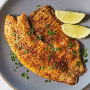 A plate with pan fried tilapia and two lemon wedges and herb garnish.