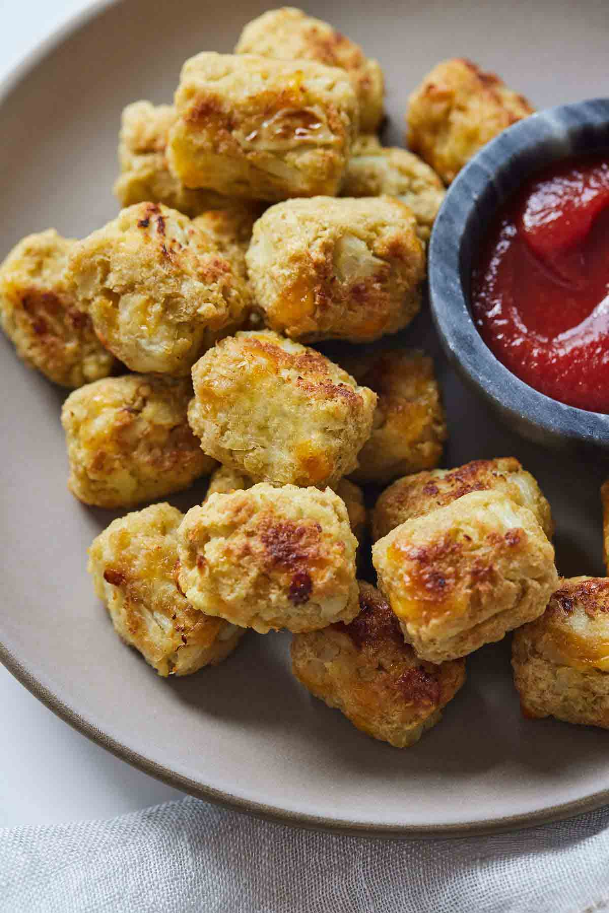 Overhead view of a plate of cauliflower tater tots with a side of ketchup.