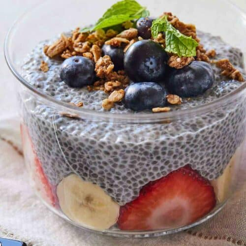 A small bowl of chia pudding with strawberries and banana slices inside and blueberries, granola, and mint on top.