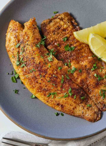 Overhead view of a grey plate with pan fried tilapia with two lemon wedges on the side.